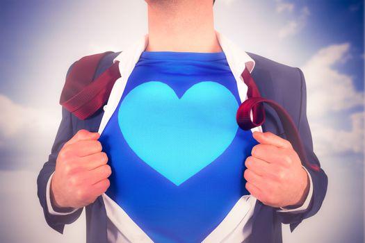 Businessman opening his shirt superhero style against blue sky