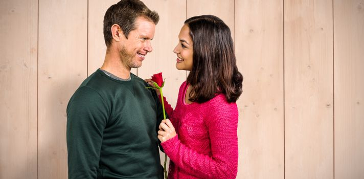 Smiling couple with red rose  against wooden planks
