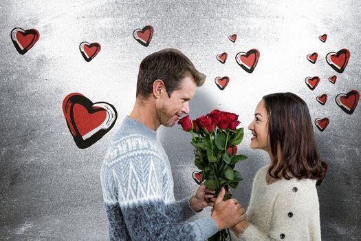 Romantic couple holding red roses against blackboard