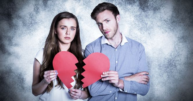 Couple holding broken heart against grey background