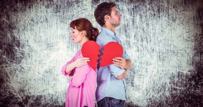 Couple holding a broken heart against grey background