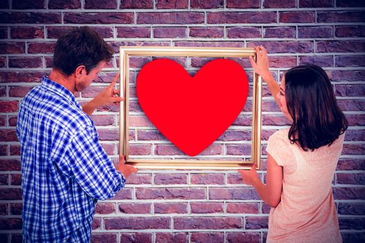 Couple holding picture frame against red brick wall