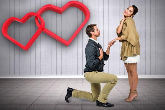 Man proposing woman while kneeling against grey room