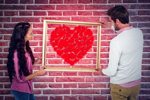Smiling couple holding picture frame  against red brick wall