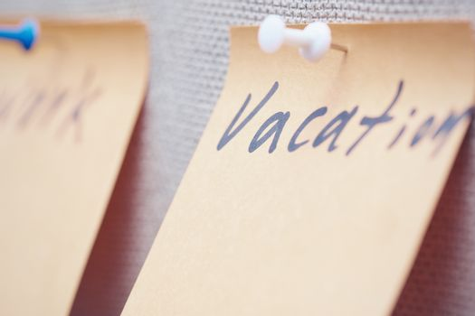 Adhesive note with Vacation text on a label