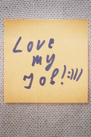 Adhesive note with Love my job text on a bulletin board