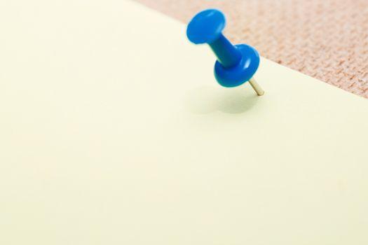 Adhesive note and blue pushpin. Close-up view