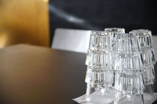 Clean drinking glasses stacked on a black table in a cafe.