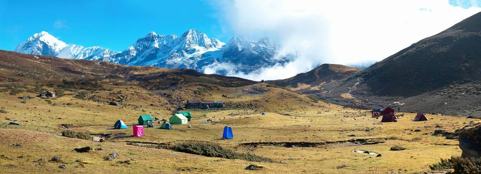 Campsite with tents on the top of high mountains, covered by snow. Kangchenjunga, India.