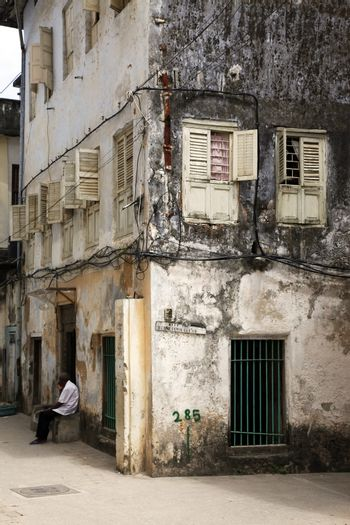 Stone Town, Tanzania - December 30, 2015: A man sits at the door of his shop with gifts for tourists in Stone Town, Zanzibar. Tanzania