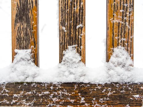 Three wooden rungs or spokes covered with snow