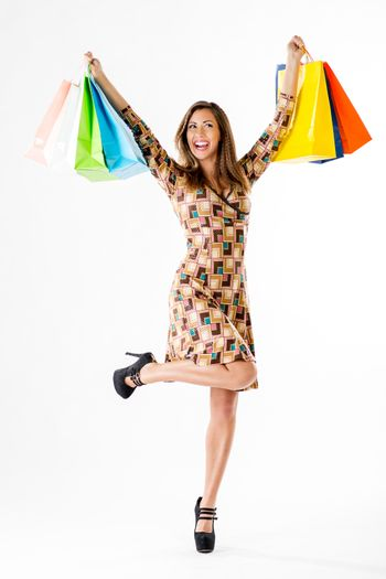 Beautiful cheerful woman with many multi colored shopping bags.  White background.