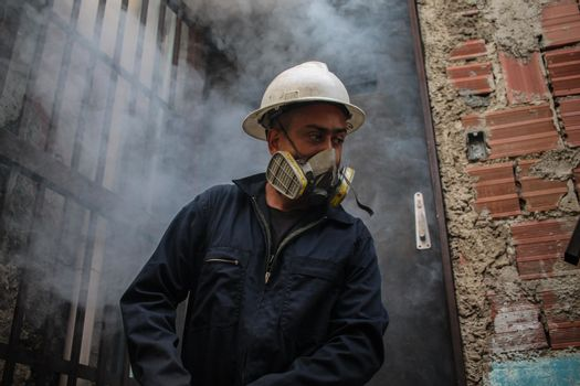 VENEZUELA, Caracas: A member of a fumigation crew exits a home after exterminating Aedes mosquitoes carrying the rapidly spreading Zika virus in the slums of Caracas, Venezuela on February 3, 2016. As of February 4, there have been reports of at least 255 cases of the rare Guillain-Barre syndrome — which causes the immune system to attack the nerves — potentially linked to the Zika virus in Venezuela.