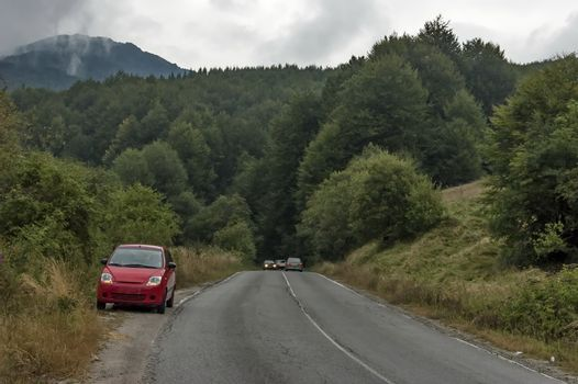 Picturesque road with car through Balkan mountain in cloudy day