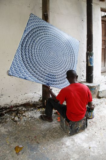 Stone Town, Zanzibar, Tanzania - December 30, 2015:  The artist paints a picture of the street Stone Town, Zanzibar