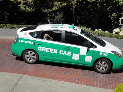 San Francisco, USA - July 22 2010: Toyota Prius Hybrid Taxi on the famous Lombard Street. Green Cab (SF Green Cab) is an Ecological Taxi company located in San Francisco, California