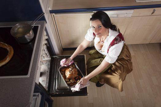 bavarian woman cooking a pork leg