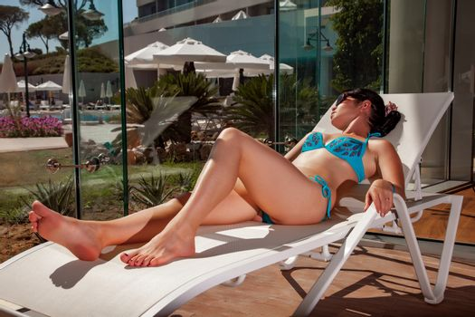 Women on a sun lounger beside the indoor pool