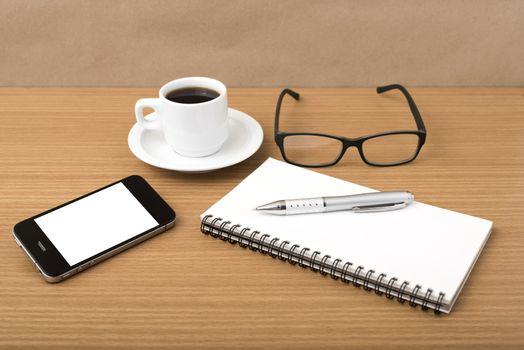 coffee,phone,notepad and eyeglasses