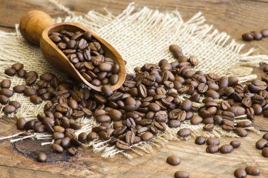 Coffee beans in wooden scoop