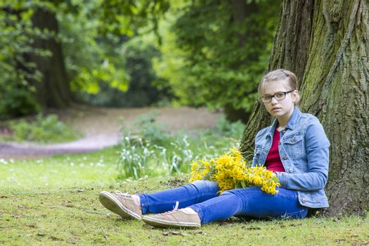 girl with big bouquet of spring flowers sitting in the park