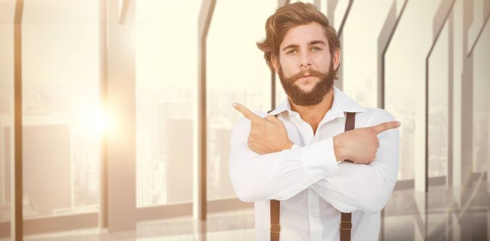 Confident hipster pointing sideways with arms crossed against room with large window looking on city