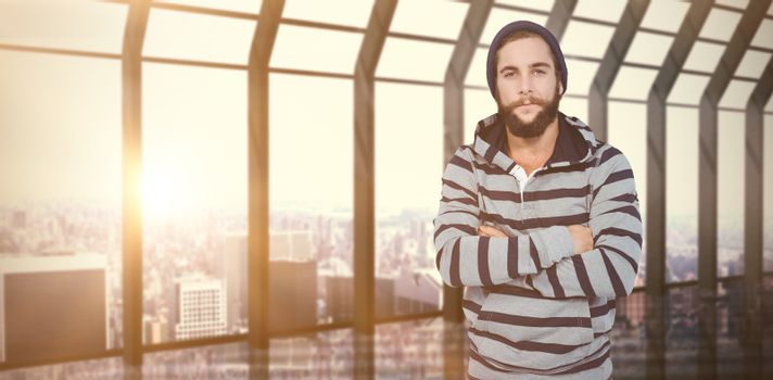 Portrait of hipster with hooded shirt against room with large window looking on city