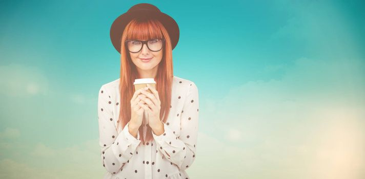 Smiling hipster woman drinking coffee against blue green background