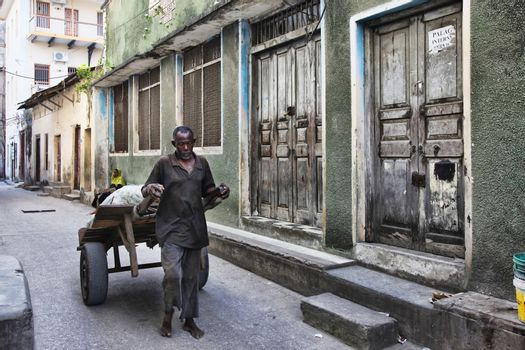 Stone Town (Zanzibar), Tanzania - January 1, 2016: unknown African man with a trolley in Stone Town, Zanzibar.