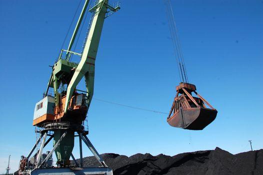 Dockside cargo craine loading coal at Kolyma river port