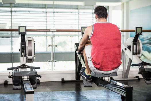 Muscular man on rowing machine