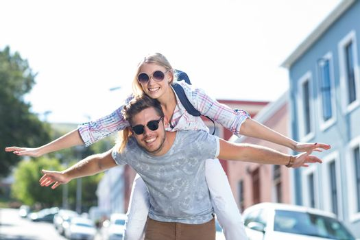 Hip man giving piggy back to his girlfriend