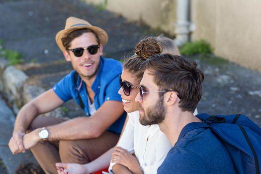 Hip friends sitting on sidewalk