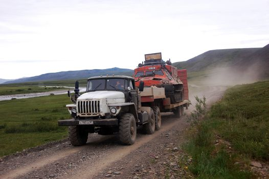 Truck carries all-terrain tracked vehicle at gravel road tundra