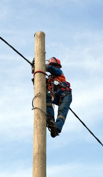 electrician installs insulated wire for electric main with the use of special tools