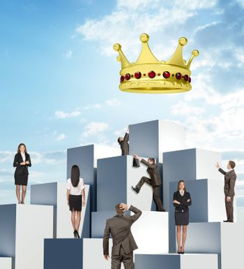 Set of business people climbing pile of boxes for big gold crown