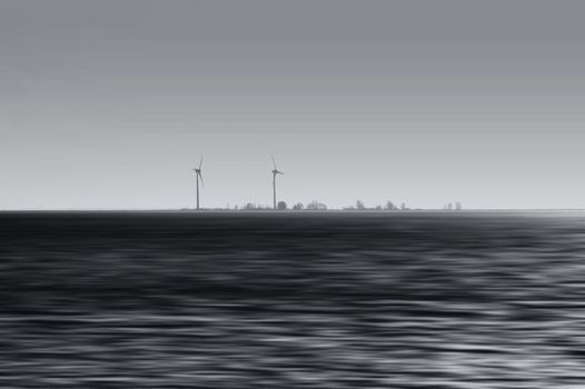 The abstract blurred sea with an island and wind turbines on it.