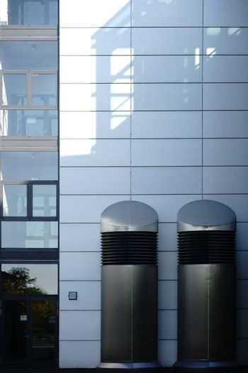 Two large ventilation hoods stainless steel stand next to the entrance of a modern building.