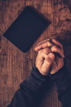 Folded hands of Christian man praying