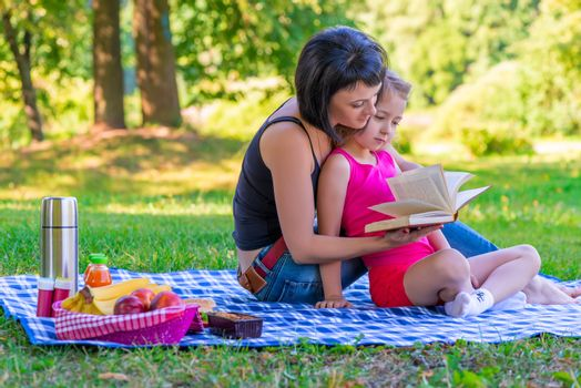 Mom and daughter reading a book on the lawn in the park