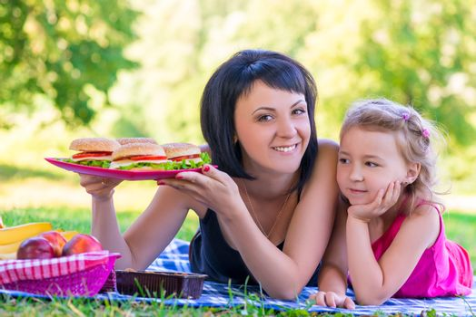 young beautiful mother holding a plate with burgers