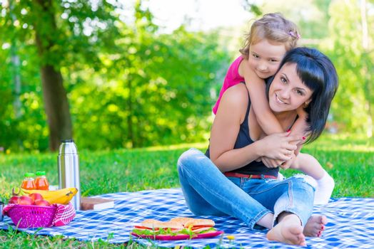 little daughter hugging her mother relaxing in the park