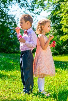 preschool age children with soap bubbles outdoors