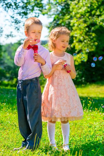 girl and boy with soap bubbles in the park