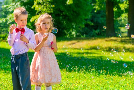 horizontal shot child with soap bubbles outdoors