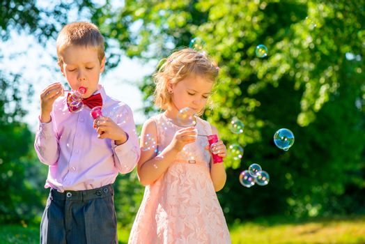 girl and her friend with soap bubbles in the park