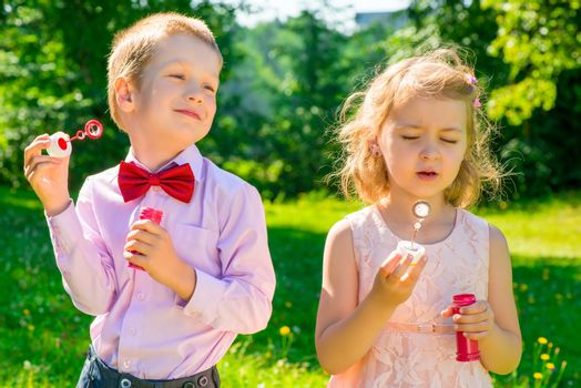 two children in a park with soap bubbles in the hands