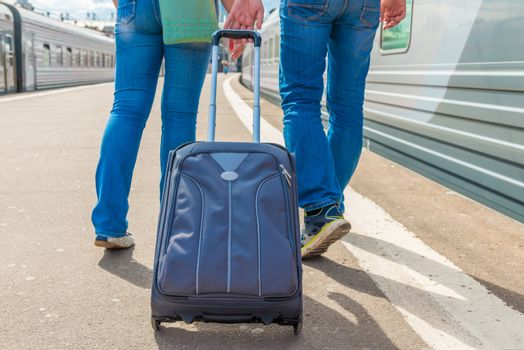 couple with a suitcase embarks on a journey on the train