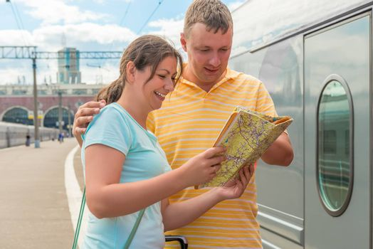 happy couple chooses a direction map for travel on the train