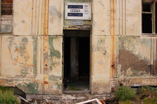 Old information sign above abandoned building entrance